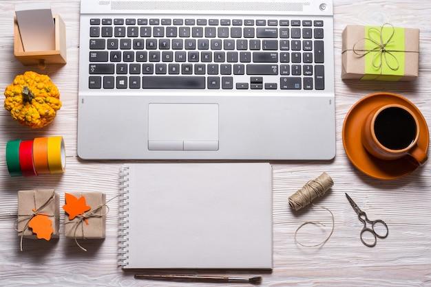 Computador e elaboração de ferramentas na mesa de madeira