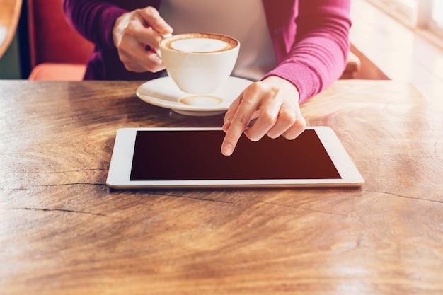 Computador e taça touchscreen de mão mulher com café no café com tom vintage.