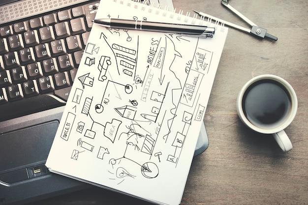 Computador, gráfico no caderno, caneta e café em uma mesa de madeira