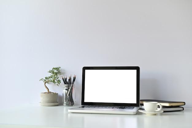 Computador laptop de maquete e material de escritório e pequenos bonsais no espaço de trabalho.
