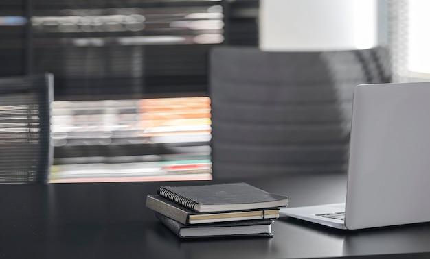 Computador laptop de maquete na mesa superior preta em um escritório moderno