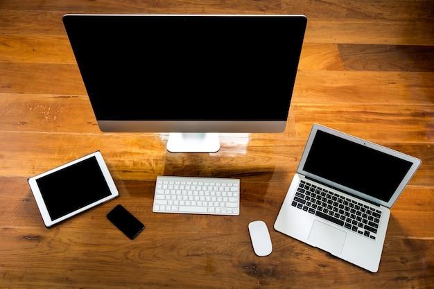 Computador, laptop e tablet vista de cima sobre uma mesa de madeira