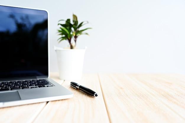 Computador laptop moderno com caneta e suculenta na mesa de madeira na vista de fundo do escritório