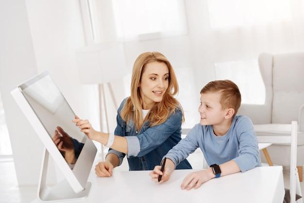 Computador moderno. menino alegre e inteligente sorrindo e olhando para o computador enquanto está sentado com sua mãe na frente dele