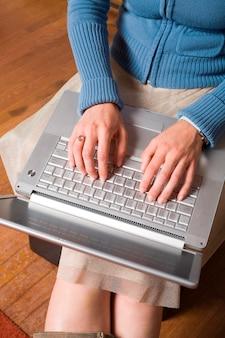 Computador no colo de mulher jovem