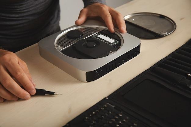 Computador pessoal aberto na mesa branca no laboratório de conserto de serviços eletrônicos, close-up, mestre leva driver de bit