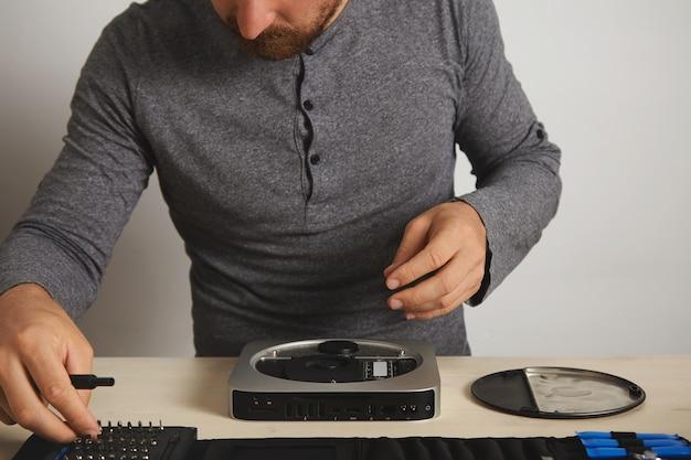 Computador pessoal aberto na mesa branca no laboratório de reparo de serviço eletrônico, mestre leva o driver de bit