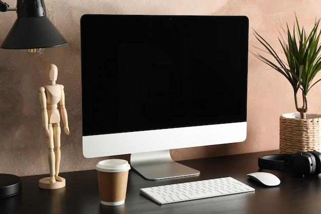 Computador, planta e madeira homem na mesa de madeira. sala de trabalho