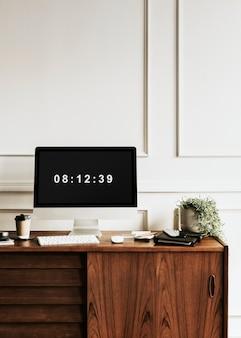 Computador por um planejador diário em uma mesa de madeira