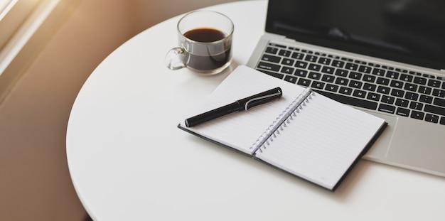 Computador portátil aberto com material de escritório em local de trabalho confortável