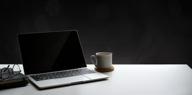 Computador portátil aberto com xícara de café e notebook na mesa branca e fundo da parede em branco