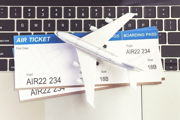 Computador portátil, avião e dinheiro na mesa. conceito de reserva de bilhetes online