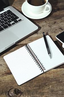 Computador portátil, bloco de notas e caneta em cima da mesa com uma xícara de café