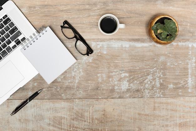 Computador portátil; bloco de notas em espiral; óculos; chá preto e planta na mesa de madeira