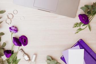Computador portátil; brincos; alianças de casamento; relógio de pulso; lixador de unha; envelope; eustoma flores e diário em fundo de madeira