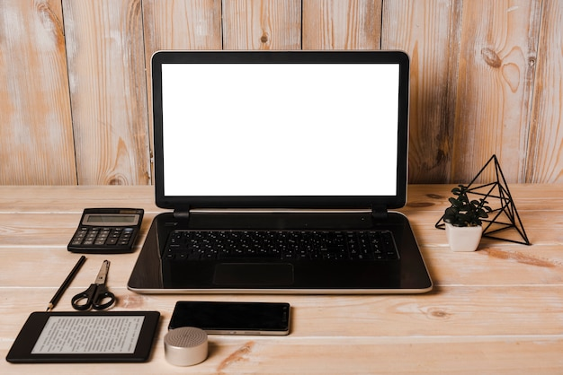 Computador portátil; calculadora; lápis; tesoura; telefone celular e leitor de ebook na mesa de madeira