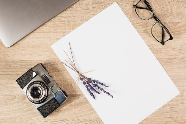 Computador portátil; câmera; óculos e papel em branco com galho de lavanda na mesa de madeira