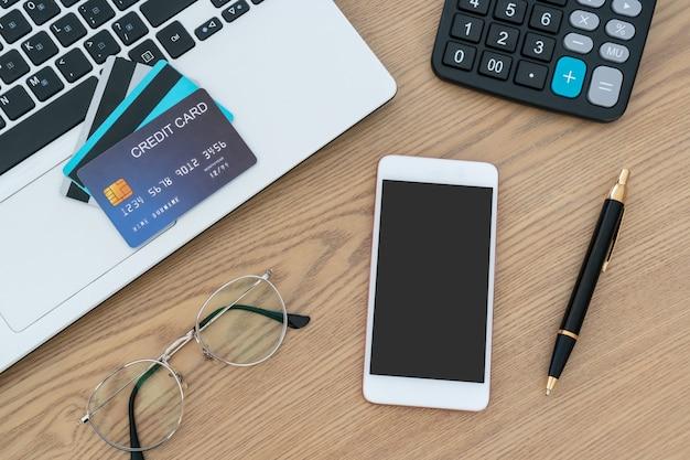 Computador portátil, cartões de crédito, calculadora, caneta de caderno e óculos em cima da mesa, conta e conceito de poupança.