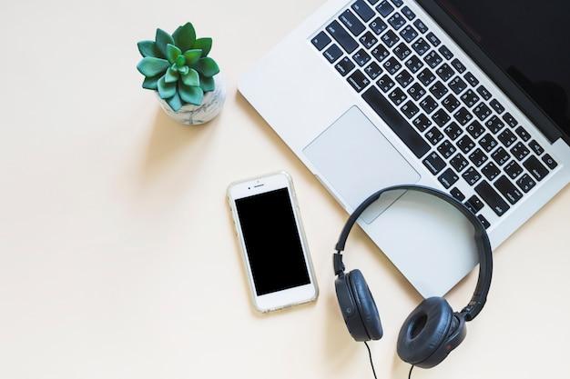Computador portátil; celular e fone de ouvido com planta de cacto em fundo bege