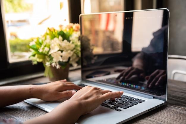 Computador portátil com as mãos da mulher na mesa de madeira perto de janelas