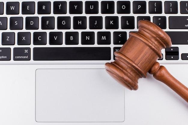 Computador portátil com martelo de tribunal no teclado. close up, vista de cima.