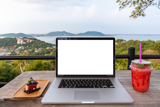 Computador portátil com morango e bolo na mesa de madeira sobre a vista da cidade de montanhas