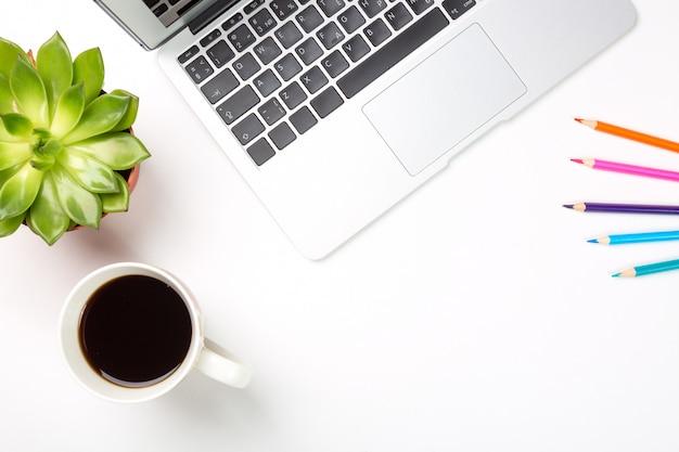 Computador portátil com planta em uma panela, xícara de café e lápis coloridos em fundo branco.