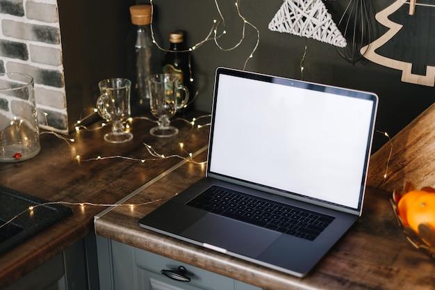Computador portátil com simulação de tela em branco branca, na mesa da cozinha com decoração de natal.