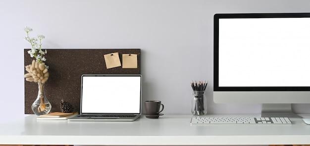 Computador portátil com tela em branco, colocando na mesa de trabalho que rodeado por monitor de computador,