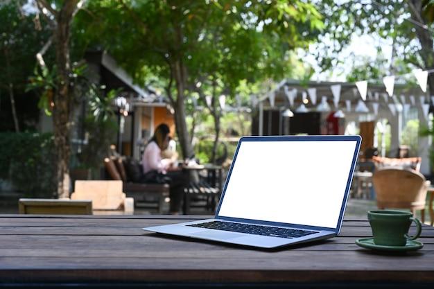 Computador portátil com tela em branco e xícara de café de madeira no aconchegante café ao ar livre.