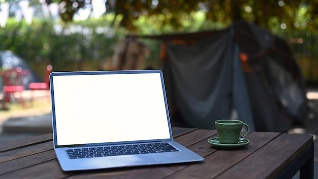 Computador portátil com tela em branco e xícara de café na mesa de madeira perto da barraca de acampamento.