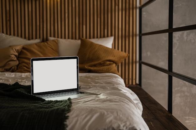 Computador portátil com tela em branco na cama com travesseiros e lençóis.
