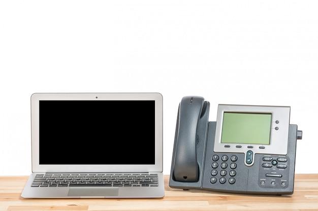 Computador portátil com telefone ip moderno na mesa de madeira clara