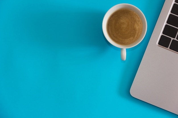 Computador portátil com uma xícara de café sobre fundo azul. conceito de escritório em casa. vista do topo. postura plana. copie o espaço.