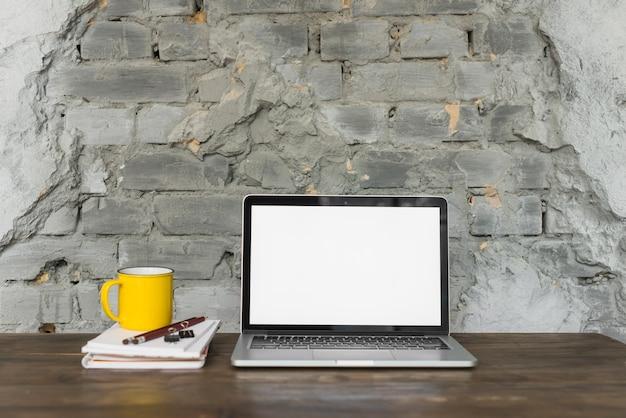 Computador portátil; copo amarelo; e artigos de papelaria na mesa de madeira
