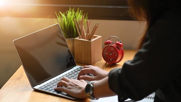Computador portátil de digitação feminino na mesa.