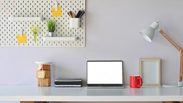 Computador portátil de espaço de trabalho confortável, café, lanche, placa de peg e material de escritório na mesa de trabalho.