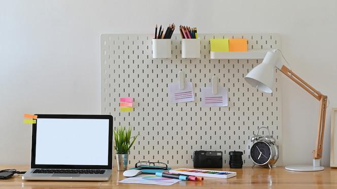 Computador portátil de espaço de trabalho criativo e acessório elegante na mesa.