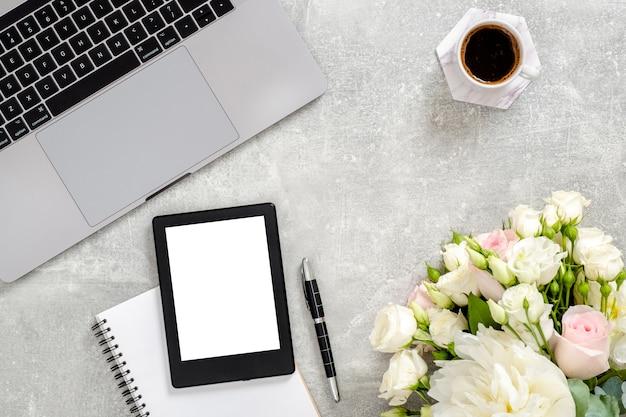 Computador portátil de espaço de trabalho feminino, tablet de tela de maquete de espaço de cópia em branco, xícara de café, diário, flores em pedra de concreto.