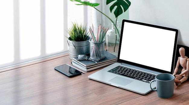 Computador portátil de maquete com tela em branco e suprimentos na mesa de madeira.