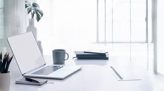Computador portátil de maquete com tela em branco na mesa
