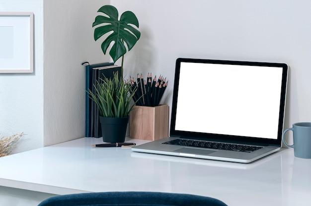 Computador portátil de maquete com tela em branco sobre a mesa na sala de escritório moderno.