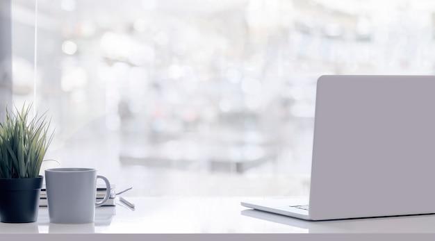 Computador portátil de maquete na mesa superior branca com desfoque de fundo.