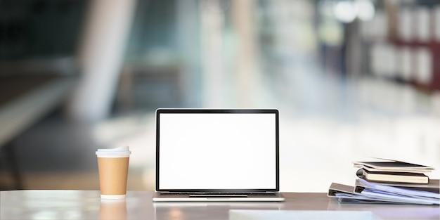 Computador portátil de maquete, xícara de café de papel, arquivo de documento na mesa de negócios com tela vazia.