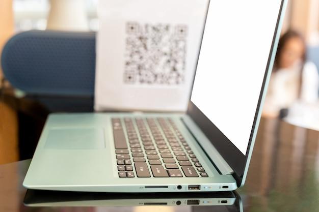 Computador portátil de negócios na mesa do balcão com código qr de desfoque