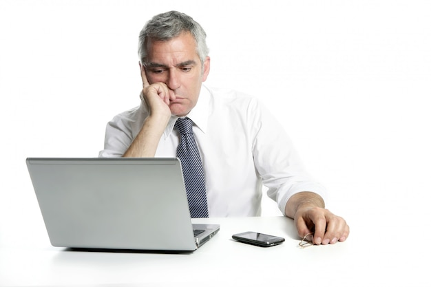 Computador portátil de pensamento sênior triste do homem de negócios