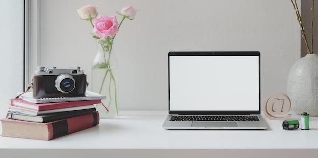 Computador portátil de tela em branco aberto com câmera com vaso de rosas e xícara de café