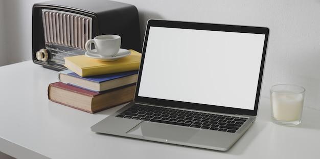 Computador portátil de tela em branco com material de escritório e rádio vintage no escritório branco mínimo