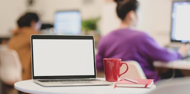 Computador portátil de tela em branco com material de escritório em escritório moderno