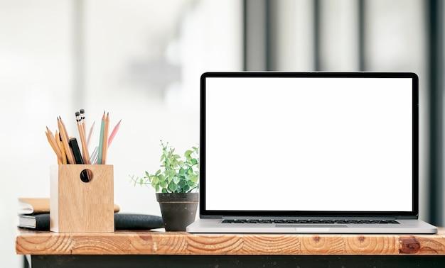Computador portátil de tela em branco de maquete com estacionário na mesa de madeira, tela em branco para design gráfico.
